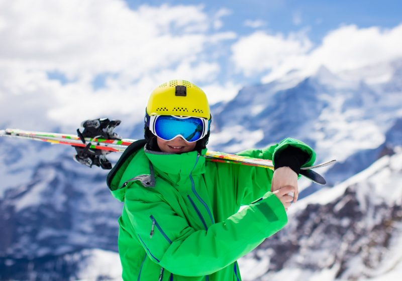 Child skiing in mountains. Active teenager kid with safety helmet goggles and poles. Ski race for young children. Winter sport for family. Kids ski lesson in alpine school. Young skier racing in snow