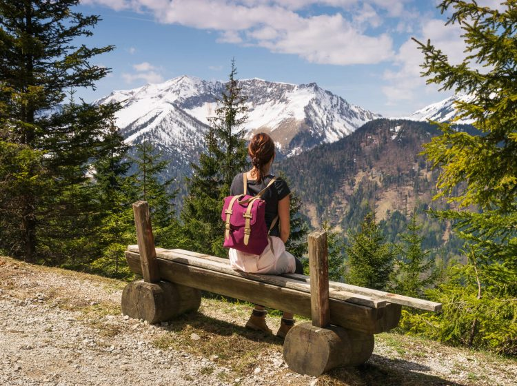 Girl relaxing after hike looking to mountain view. Traveler sitting on wooden bench enjoying beautiful mountain view. Travel. traveler. Mountain view. Hiking in mountain. Girl hiker relaxing after hike.